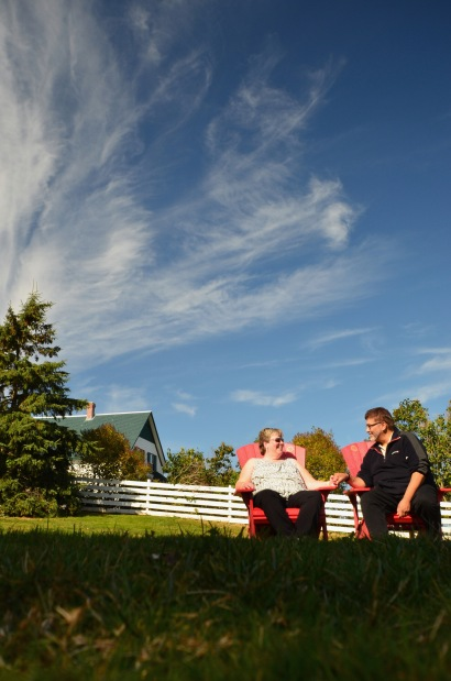 Couple sitting on red chairs in front of green house with white picket fence.