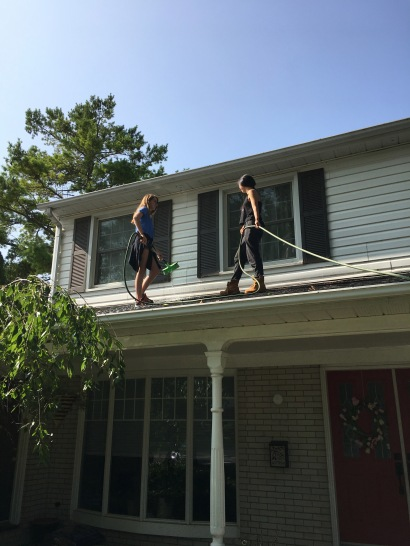 Window cleaners on the roof of a house
