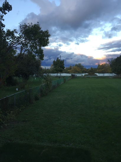 View of canal across yard with setting sun