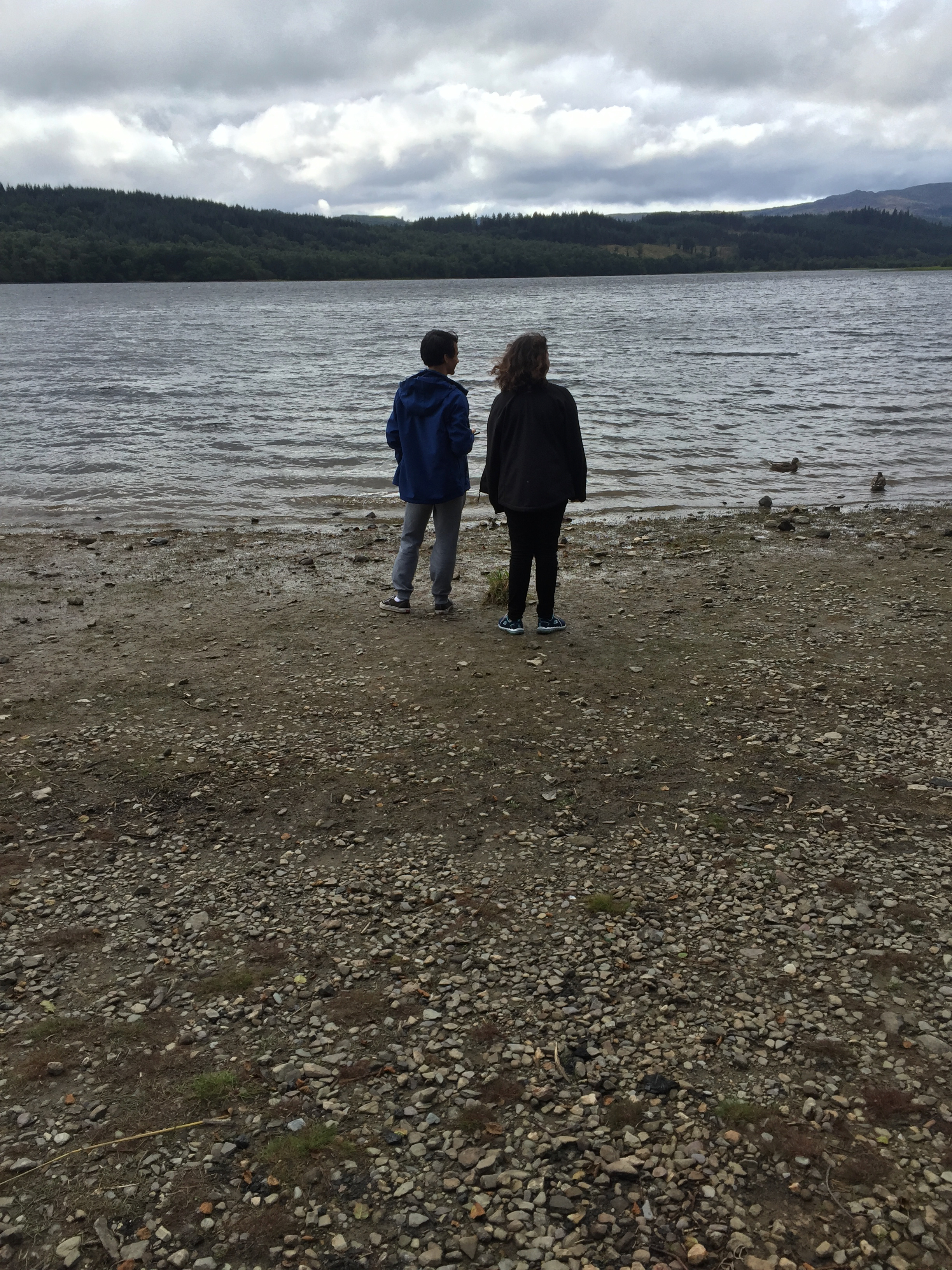 Two young people looking out across a lake
