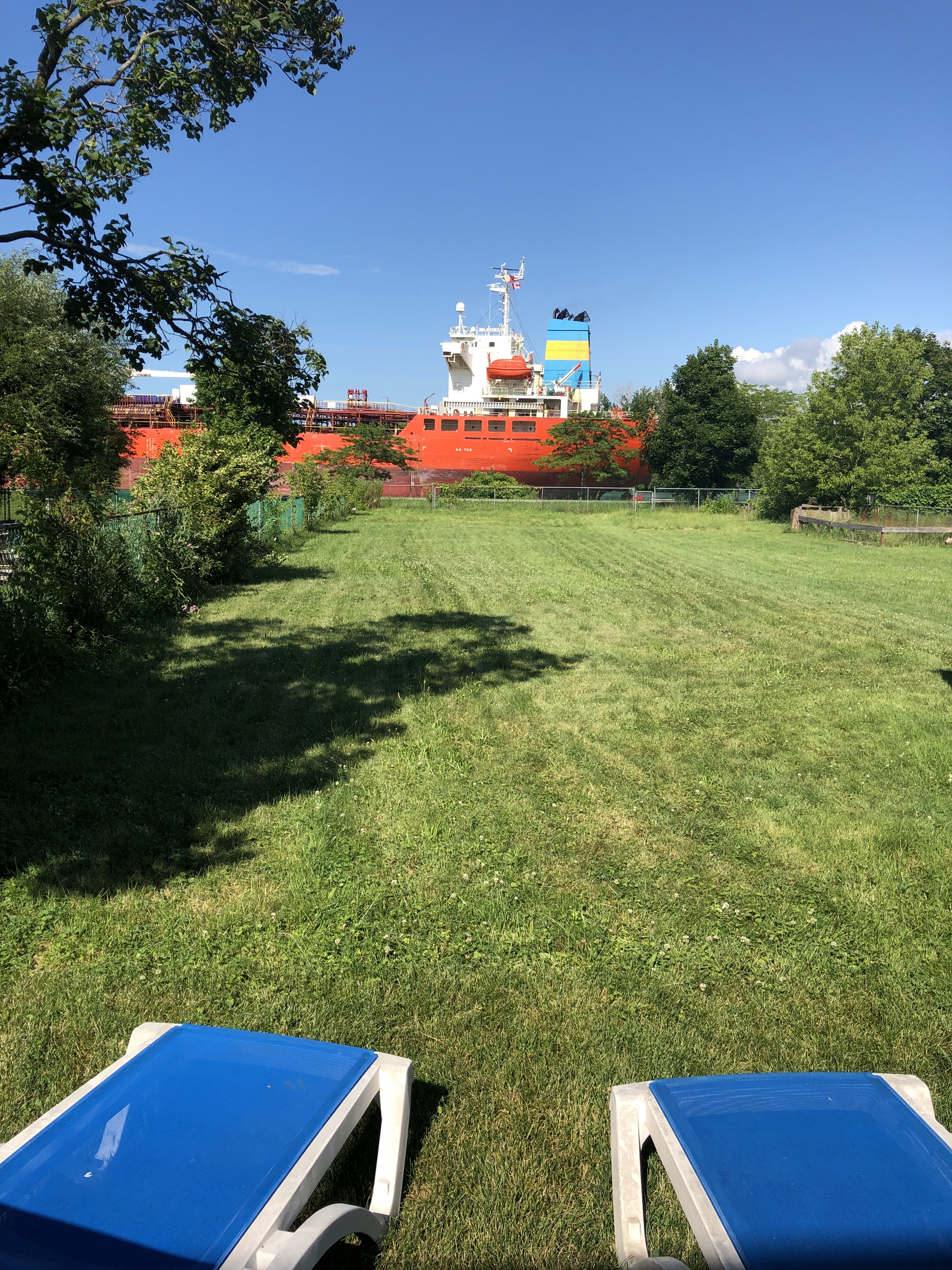 Lawn chairs overlooking backyard with the view of a large ship